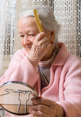 Old smiling woman combing her hair