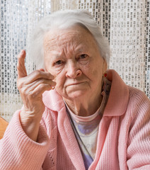 Portrait of  old woman in angry gesture