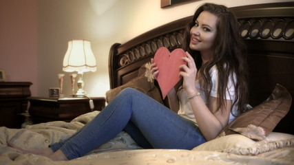Woman with big red heart lying on the bed and smiling.