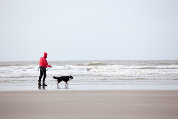 man and dog on cold beach