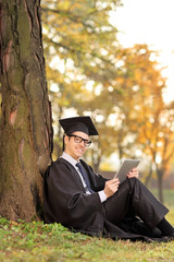 Graduate student holding a tablet in park