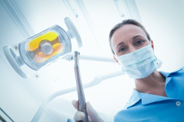 Female dentist in surgical mask holding dental tool