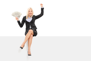 Joyful businesswoman holding money seated on panel