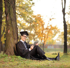 Graduate student holding a tablet seated on grass