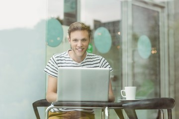 Smiling student using laptop in cafe