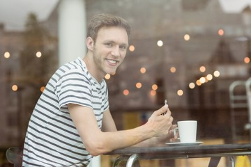 Smiling student sitting with a hot drink
