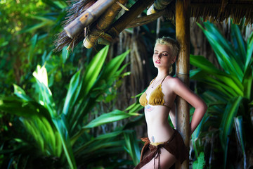 Young beautiful girl in a bamboo hut in a tropical jungle.