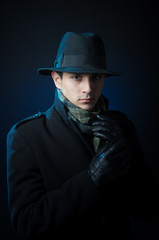 Young man in black trench coat standing in the darkness