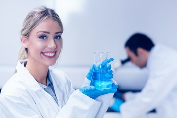 Science student holding blue chemical in beaker