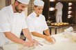 canvas print picture - Team of bakers kneading dough