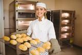 Baker smiling at camera holding rack of rolls
