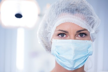 Dentist in surgical mask and cap looking at camera