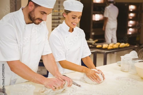 canvas print picture Team of bakers kneading dough