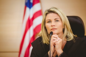 Portrait of a serious judge with american flag behind her