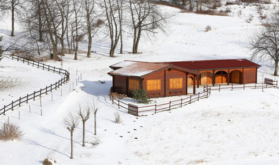 wooden chalet in the mountains and snowy