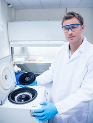 Chemist wearing safety glasses and using a centrifuge