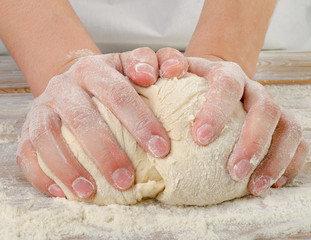 Hands closeup kneading dough