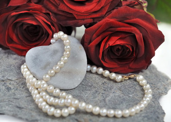 collier de perles sur cœur et roses rouges