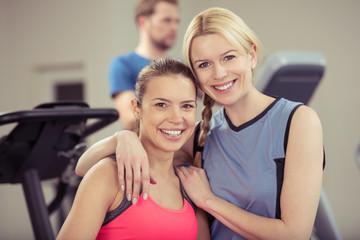 zwei lachende frauen im fitness-studio