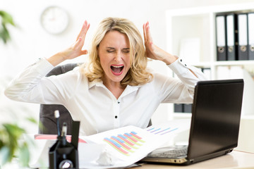Stressed business woman screaming loudly working in office