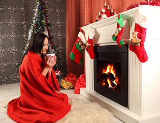 smiling woman in with christmas tree in winter house