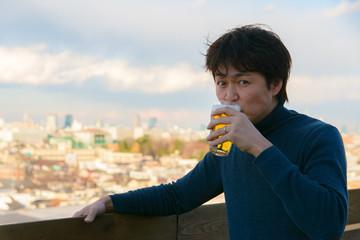 屋外でビールを飲む男性