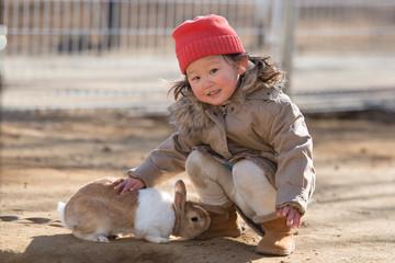 ウサギを撫でる少女