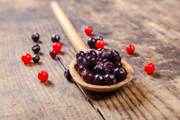 black currant in wooden spoon on rustic background