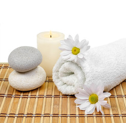 Spa decoration with stones, candle, towel and daisies