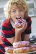 Boy Eating Iced Donut In Kitchen