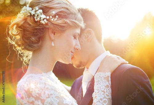 Young wedding couple on summer meadow - 76005750
