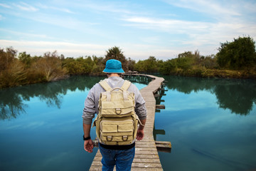 tourist man walking across wooden bridge over glossy blue lake