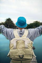 tourist man with outstretched arms on glossy blue lake