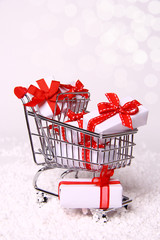 Shopping cart and gifts on white