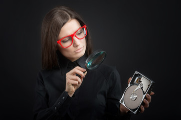 Girl looking at hard disk drive through magnifying glass