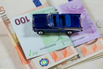 blaues Auto mit Euroscheinen