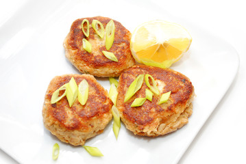 Fish Cakes Served with Lemon and Scallions