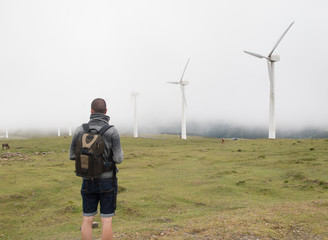Man contemplating wind turbines in nature