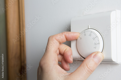 Close Up Of Female Hand On Central Heating Thermostat - 76008934