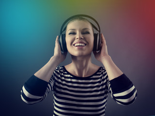 Party girl in earphones. Pretty smiling woman listening music