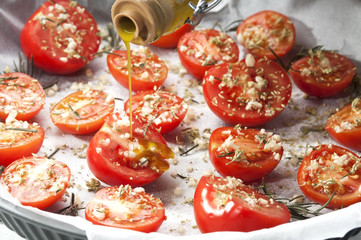 seasoning tomatoes in a baking tray
