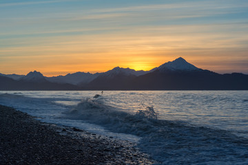 A surfer paddles out in waves on Kachemak Bay