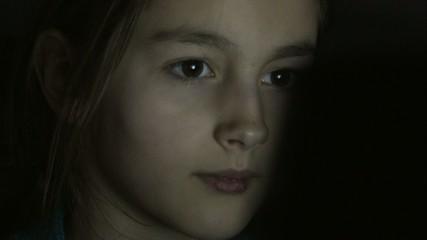 Closeup shot of little girl eye surfing internet at night
