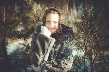 Beautiful young woman smiling in a pine forest