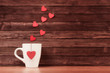 White cup with heart shapes over vintage wooden background - 76011575