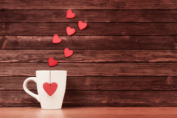 White cup with heart shapes over vintage wooden background
