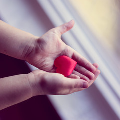 Child is holding a small heart