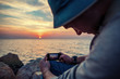 traveler making photo with mobile phone at sunset