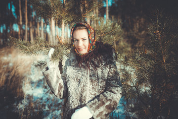 Beautiful young woman taking a walk through the pine forest