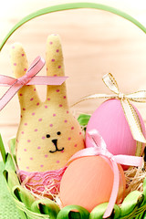 Easter Bunny and painted Eggs in basket on wooden background